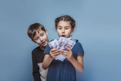 Girl holding money bills in the hands of the boy Stock Photo