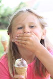 Girl holding mouth and ice-cream Stock Image