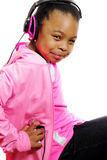 Girl Holding MP3 Player Listens To Music. A young African American girl in jeans holding her mp3 player while sitting, smiling and listening to music.  Isolated Stock Photography