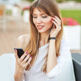 Girl holding a MP3 player Royalty Free Stock Photo