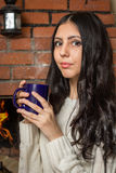 Girl holding a mug of hot tea. Girl inhales the aroma of hot tea Stock Photos