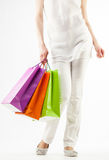 Girl holding multicolored shopping paper bags Royalty Free Stock Images