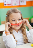 Girl Holding Mustache Made Of Clay In Classroom Stock Photography
