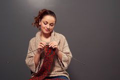 Girl holding needles and knitting scarf Royalty Free Stock Image