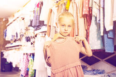 Girl holding new dress in hands in children clothes boutique Stock Photos