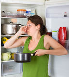 Girl holding nose near refrigerator. Brunette girl holding her nose because of bad smell from food near refrigerator at home royalty free stock image
