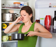 Girl holding nose near refrigerator. Girl holding her nose because of bad smell from food near refrigerator at home stock photography