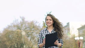 Girl holding notebook, looking in profile, walking smiling on camera. Slowly stock footage