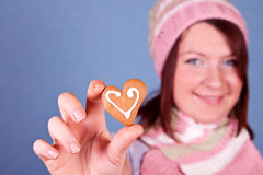 Girl holding one heart cookie Royalty Free Stock Photography