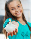 The girl is holding the onion Royalty Free Stock Photography