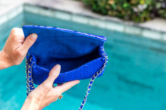 Girl holding opened luxury snakeskin python handbag on a swimming pool background. Tropical island Bali. Girl holding luxury snakeskin python handbag on a stock photography