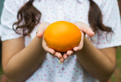 A girl holding an orange Royalty Free Stock Photos