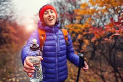 The girl is holding out a bottle of water. A woman with a backpack is giving a bottle. Trekking in autumn Stock Images