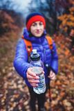 The girl is holding out a bottle of water. A woman with a backpack is giving a bottle. Trekking in autumn Stock Image