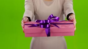 Girl holding out a box with a gift. Close up stock video