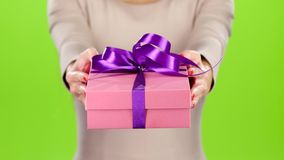 Girl holding out a box with a gift. Studio stock video footage