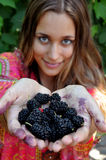 Girl holding out hands with berries royalty free stock image