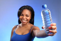 Girl holding out sharply focused bottled water Stock Photography