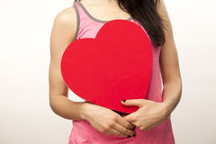 Girl holding oversized heart. Horizontal, color, close up image of a girl isolated on white and holding an oversized heart for Valentine Day stock photos