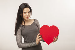 Girl holding oversized heart. Horizontal, color image of a girl isolated on white holding an oversized heart for Valentine Day royalty free stock photos