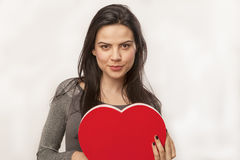 Girl holding oversized heart. Horizontal, color image of a girl isolated on white and holding an oversized heart for Valentine Day royalty free stock photography