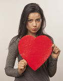 Girl holding oversized heart. Horizontal, color image of a girl isolated on white and holding an oversized heart for Valentine Day stock photography