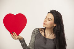 Girl holding oversized heart. Vertical, color image of a girl isolated on white and holding an oversized heart for Valentine Day stock images