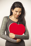 Girl holding oversized heart. Vertical, color image of a girl isolated on white and holding an oversized heart for Valentine Day royalty free stock photography