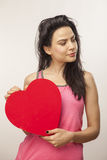 Girl holding oversized heart. Vertical, color image of a smiling girl holding an oversized heart for Valentine Day stock image