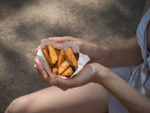 A girl holding a pack of fries in hand in the street. Small pack of potato fries, fast snack.  royalty free stock photography