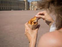 A girl holding a pack of fries in hand in the street. Small pack of potato fries, fast snack.  stock photos