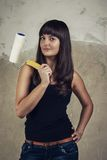 Girl holding paint roller over grunge background Royalty Free Stock Photos