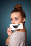 Girl holding paper with funny smiley drawing on gradient background Royalty Free Stock Photos