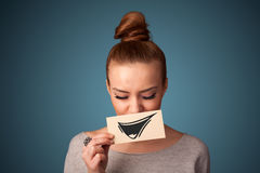 Girl holding paper with funny smiley drawing on gradient background Stock Photography