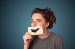 Girl holding paper with funny smiley drawing Royalty Free Stock Photos
