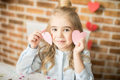 Girl holding paper hearts. Adorable smiling little girl holding two pink paper hearts Stock Image