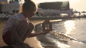 Girl holding paper house on the beach during sunset. People, dream, family, real estate and home concept. Child dreams. To live by the sea stock video footage