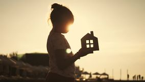 Girl holding paper house on the beach during sunset. People, dream, family, real estate and home concept. Child dreams. To live by the sea stock video