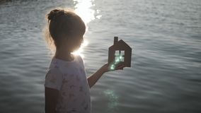 Girl holding paper house on the beach during sunset. People, dream, family, real estate and home concept. Child dreams. To live by the sea stock footage