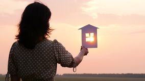 Girl holding a paper house. The sun`s rays pass through the Windows of the paper house. Slow motion stock video