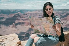 Girl holding paper map searching route. Woman hiker happy relaxing sitting on the rock grand canyon north rim. young girl with sunglasses holding paper map royalty free stock photos