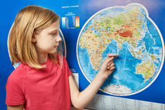 Girl holding paper plane on world map Stock Image