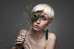 Girl holding peacock feather. Horizontal studio portrait of young attractive short-cut blond brown-eyed caucasian teenage female with turquoise earring made from Stock Photos