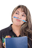 Girl holding pen with her mouth Royalty Free Stock Images
