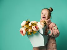 Girl holding peonies bouquet on blue background stock image