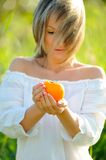 Girl holding persimmon fruit Royalty Free Stock Image