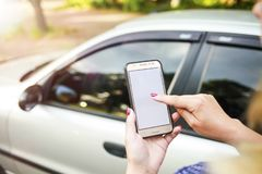 Girl holding a phone in the background of the car. Theme car rental using phone car sharing stock photo