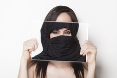 Girl holding a photo of herself wearing a burqa Royalty Free Stock Photos