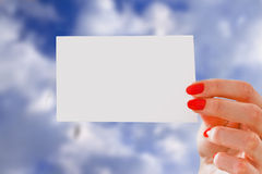Girl holding piece of paper with copyspace over blue sky Stock Photos