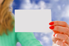 Girl holding piece of paper with copyspace over blue sky Stock Images